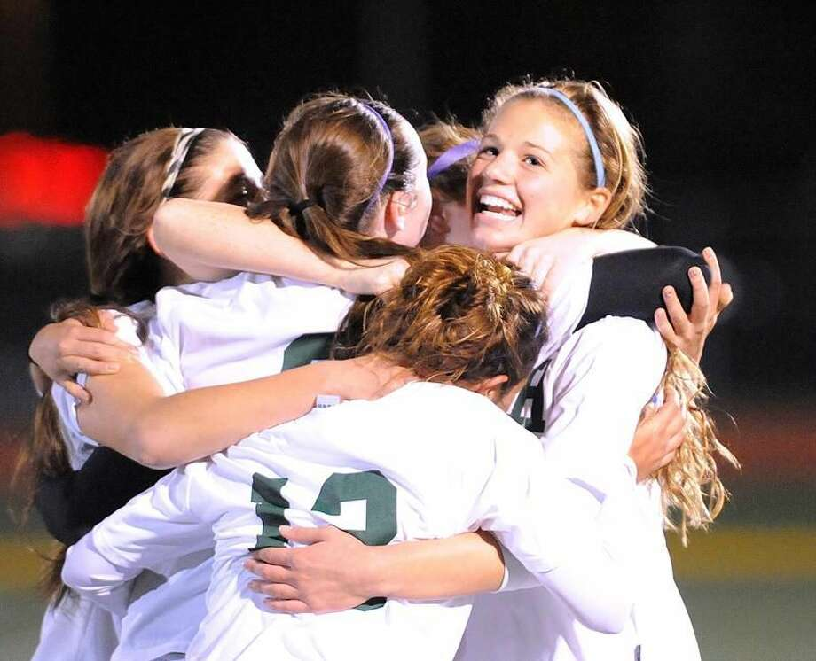File photo by Peter Casolino/Register Hamden's Rachel Ugolik (facing camera) is hugged by teammates after scoring in last year's state tournament game against Staples. Ugolik, a junior, set Hamden's career scoring record with four goals against Hand on Oct. 4.
