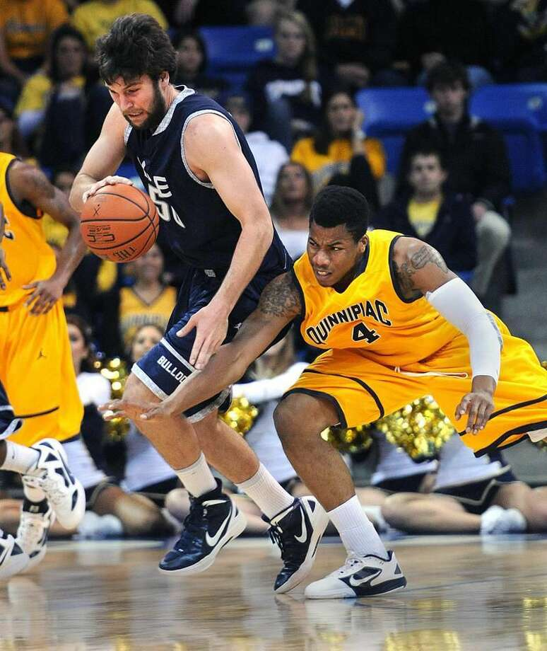 Hamden— Yale's Jeremiah Kreisberg battles for a loose ball with Quinnipiac's Ike Azotam during the first half. Peter Casolino/New Haven Register