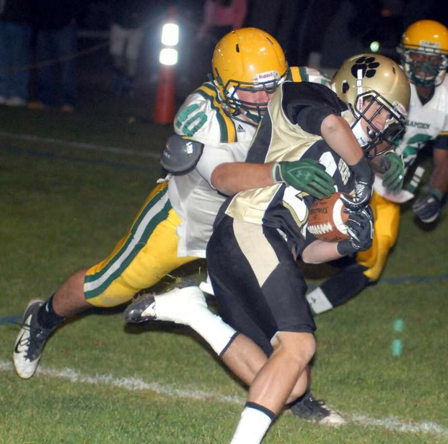 Photo by Dave Phillips Hamden's Tyler Stevens wraps up Hand's Jason Raleigh in the Green Dragons' 42-7 loss to Hand Friday night in Madison.