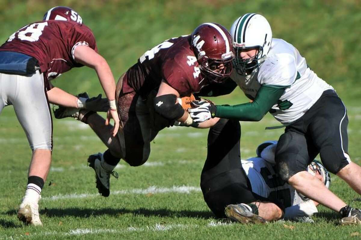 With the help of teammate Max Pantalena, left, Jim Martino of Hopkins, center, grinds out extra effort yardage against Brandon Ginnetti of Hamden Hall during fourth quarter football action Saturday at Hopkins. Photo by Peter Hvizdak/New Haven Register