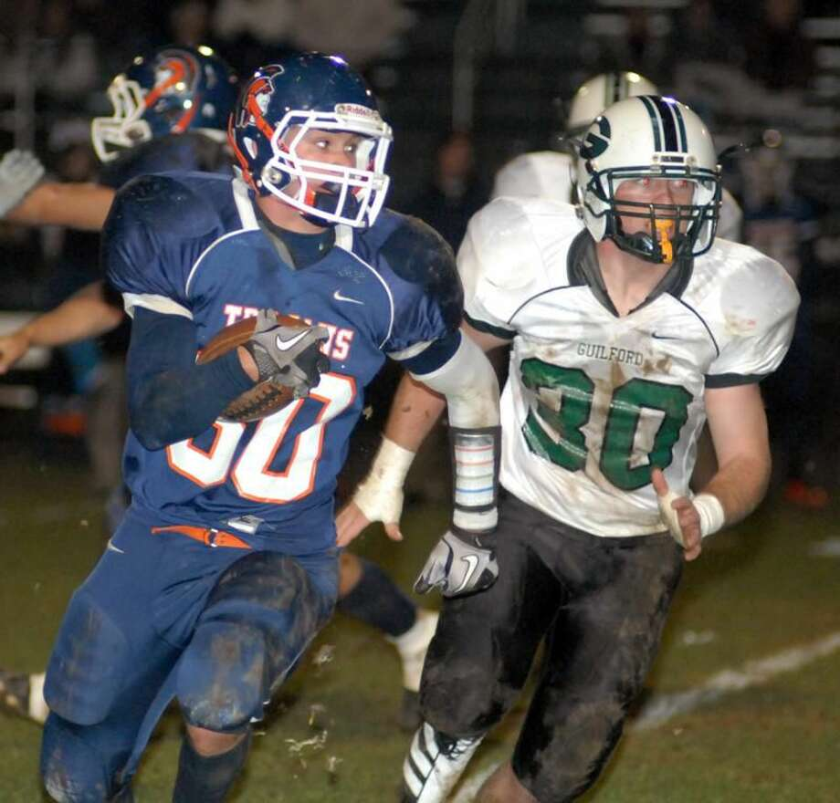 Photo by Dave Phillips Lyman Hall's Joe DeSandre runs with the ball while Guilford's J.P. Peters pursues him in the Trojans' 54-14 loss Friday night in Wallingford.