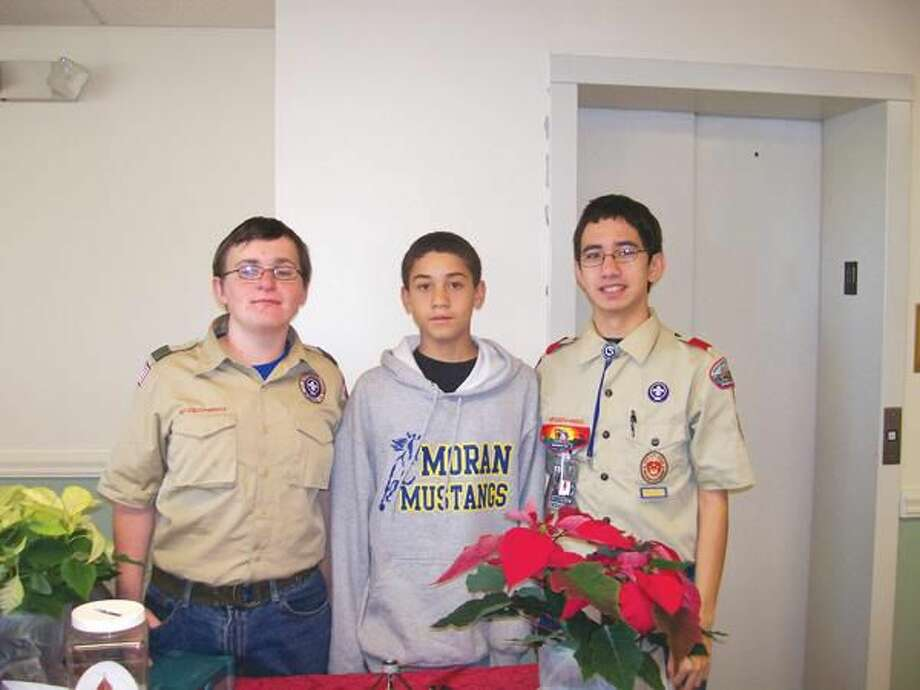 Photo by Lynn Fredricksen For members of St. Paul's Episcopal Church Boy Scouts Troop 4 poinsettia sales were booming at the parish's recent Holiday Fair. Pictured left to righ: Dominic Schaedler, Ken Nepton and Kevin Ellis.