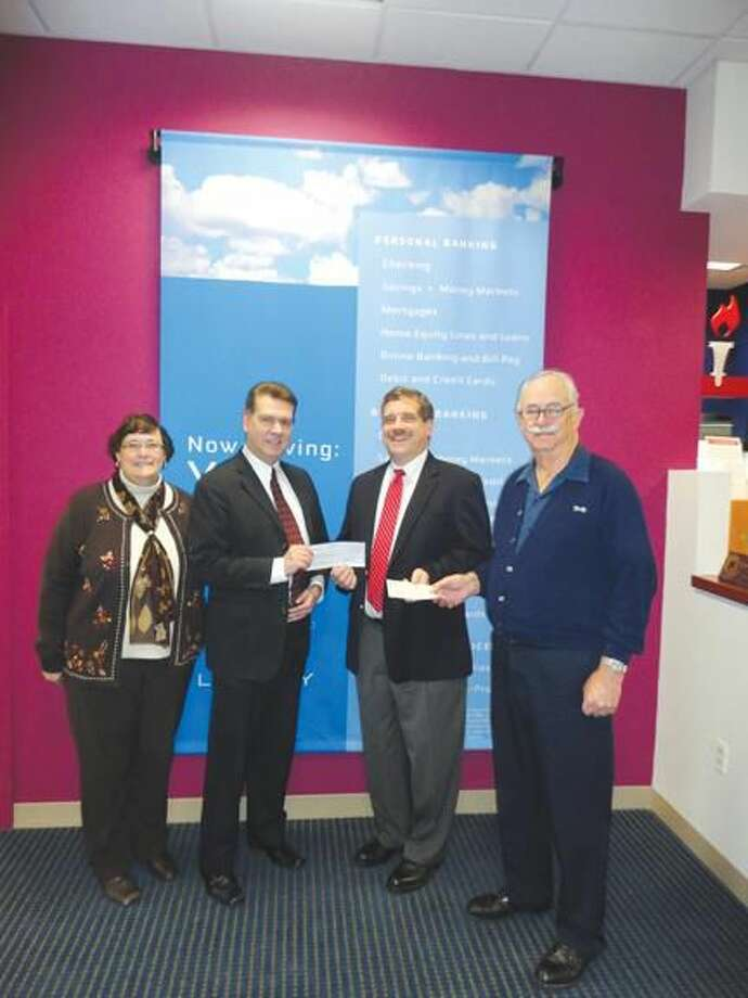 Submitted Photo Rotarian Debbie Volain, left, looks on as Liberty Bank Manager Mark Piscitelli presents Rev. Scott Morrow a holiday drive check, and Rotarian John Graef, right, hands him a new contribution.