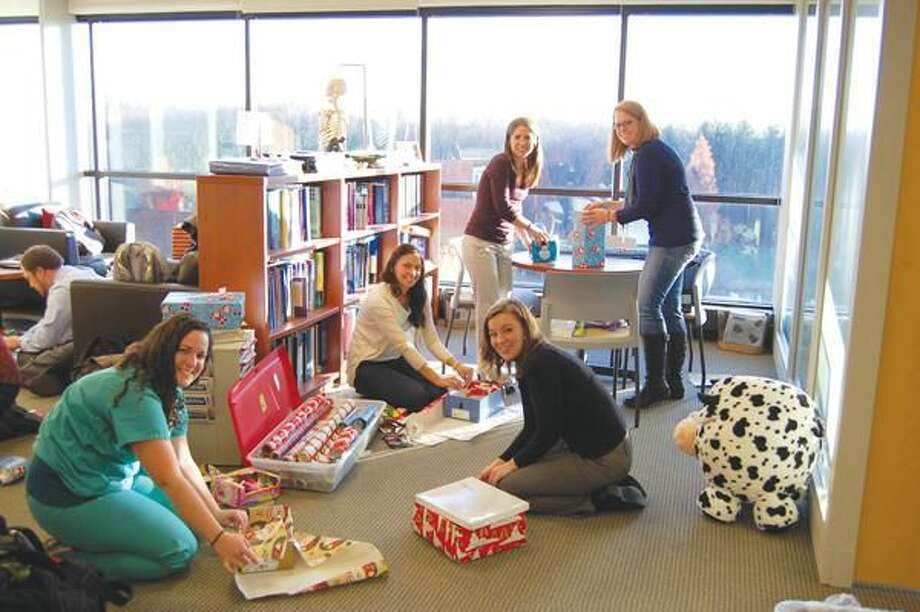 Submitted Photo Quinnipiac University physician assistant students Emma Banks, left, Madeline Santiago, Stephanie Lenihan, Sarah Normandin and Jessie Dorne wrap shoe boxes as part of Operation Christmas Child.
