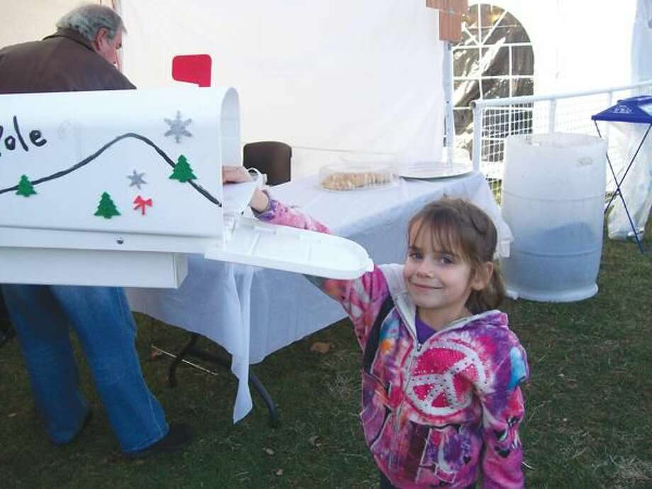 "Photo by Lynn Fredricksen Madisen Karavas, 6, of North Haven, had a great time at the Silverbells Festival in Hamden Town Center Park recently. Like many of the other children, Madisen wrote a letter to Santa and sent it ""special delivery"" straight to the North Pole via the Hamden Arts Council's mailbox."