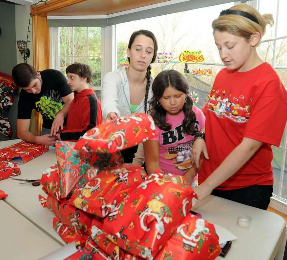 With Marissa Mulligan of North Haven, 9, second from right, North Haven High Schoo Interact Club members from left, Joe Guandalini, David Gordan, Hannah Finch and Alex Johnson, far right, wrap presents Friday to be given out at the club's Christmas party with the Department of Children and Families at Fantasia in North Haven today for foster and adopted children. The Interact Club raised $5,000 for the party. Peter Hvizdak/Register