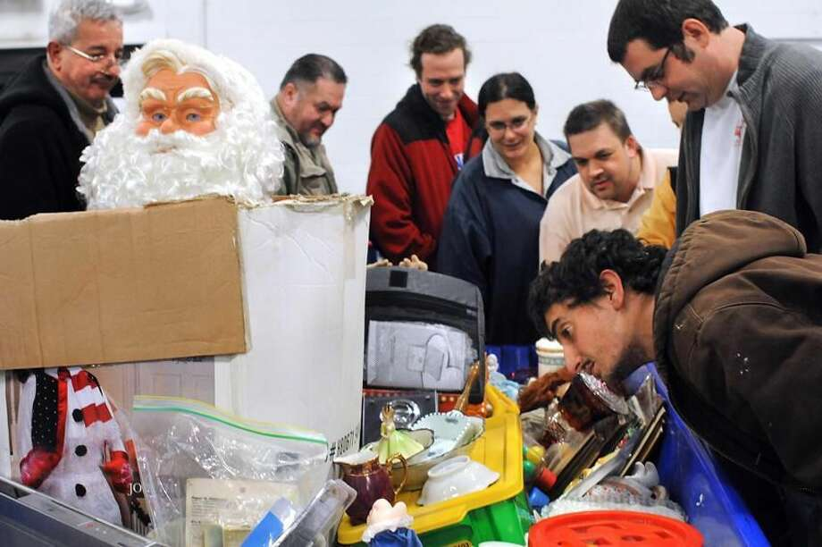 People look over the contents of a bin up for auction at the Hamden Goodwill. No touching is allowed. (Melanie Stengel/Register)