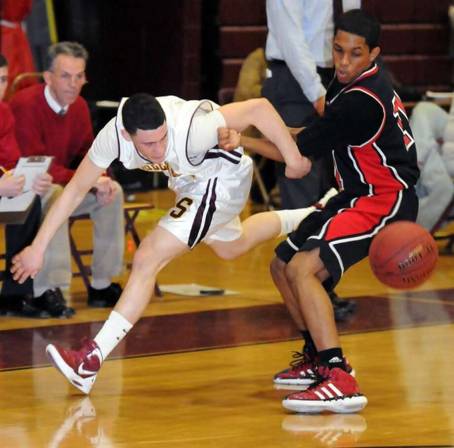 Sheehan's A.J. Pascuzzo, left, and Cheshire's Tyler Barnes battle to try and grab the basketball. Photo by Mara Lavitt/New Haven Register