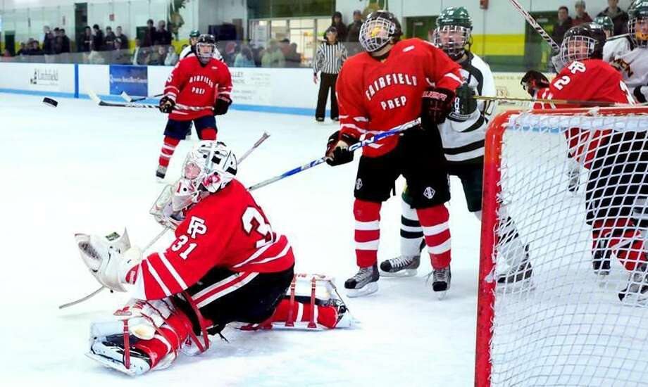 Fairfield Prep goalie Riley Wikman (left) of Fairfield Prep blocks a shot against Hamden in the first period on 12/25/2012. Photo by Arnold Gold/New Haven Register