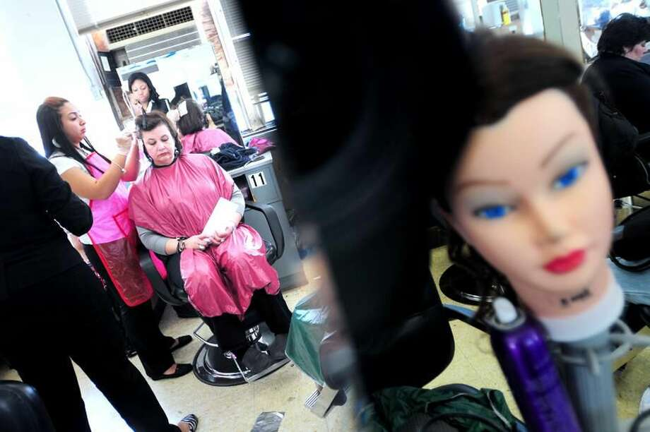 Sulaina Rodriguez, far left, 17, adds highlights to the hair of Joan Oriol in the Cosmetology and Barbering Department at Eli Whitney Technical High School in Hamden. Oriol is among a group of DCF program foster mothers from Meriden being treated to a day of pampering at the school. Arnold Gold/Register