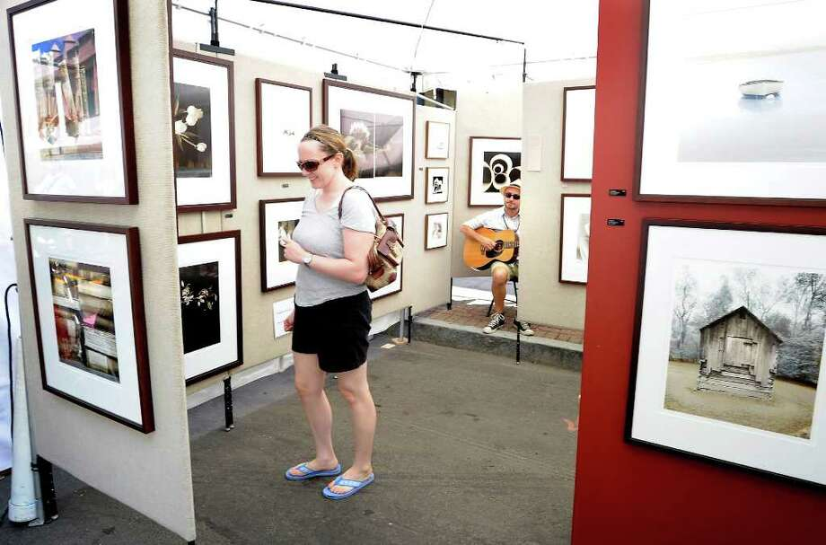 Photographer Andrew Sovjani, of Conway, Mass, plays guitar as visitors walk through his booth at the 34th annual SoNo Arts Celebration in Norwalk, Conn. on Saturday August 7, 2010. Photo: Kathleen O'Rourke / Stamford Advocate