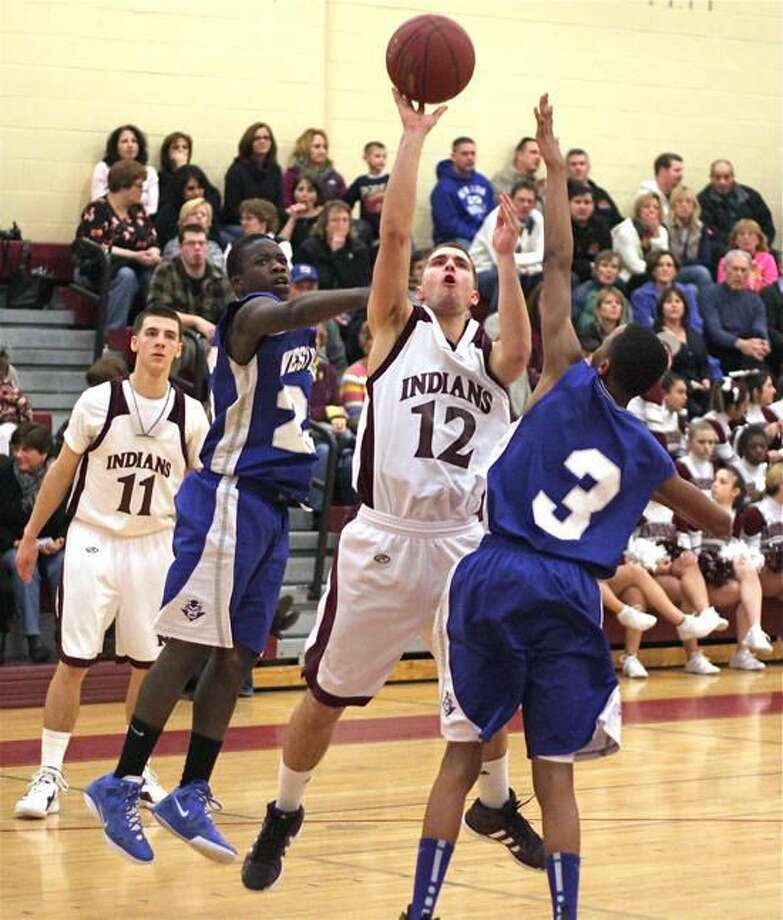 Photo by Russ McCreven North Haven's Dominic Schioppo shoots over West Haven's Gary Dudley.