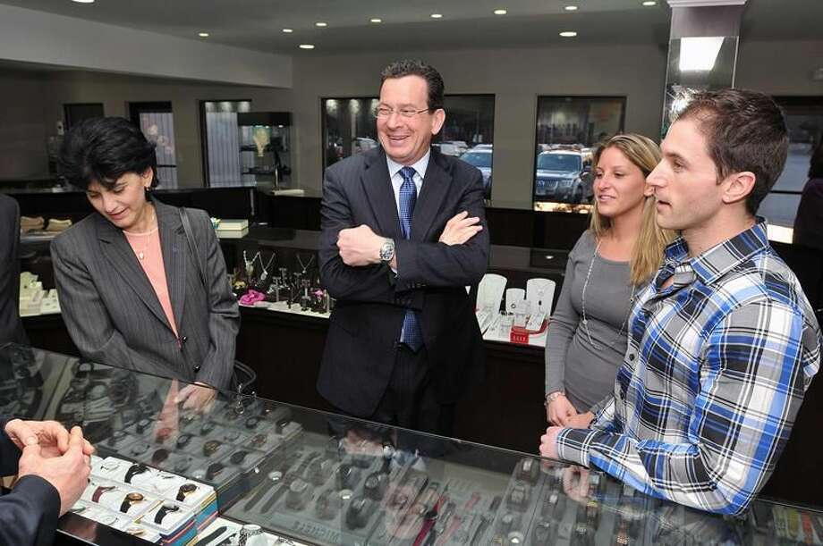 Gov. Dannel P. Malloy, center, laughs as he visits Rumanoff's Fine Jewelry in Hamden prior to a Chamber of Commerce dinner at DeMil's Restaurant. On the left is SCSU President Mary A. Papazian and on the right is Doug and Leslie Rumanoff. Peter Casolino/Register