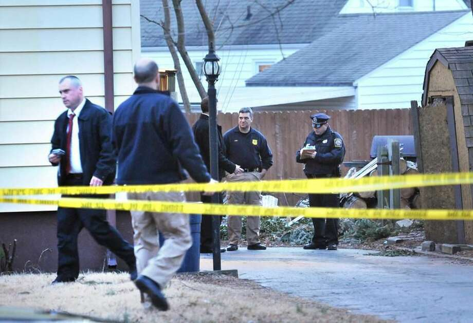Hamden police investigate behind the house at 388 Wooden St. after a woman's body was found by the homeowner there. Peter Casolino/Register