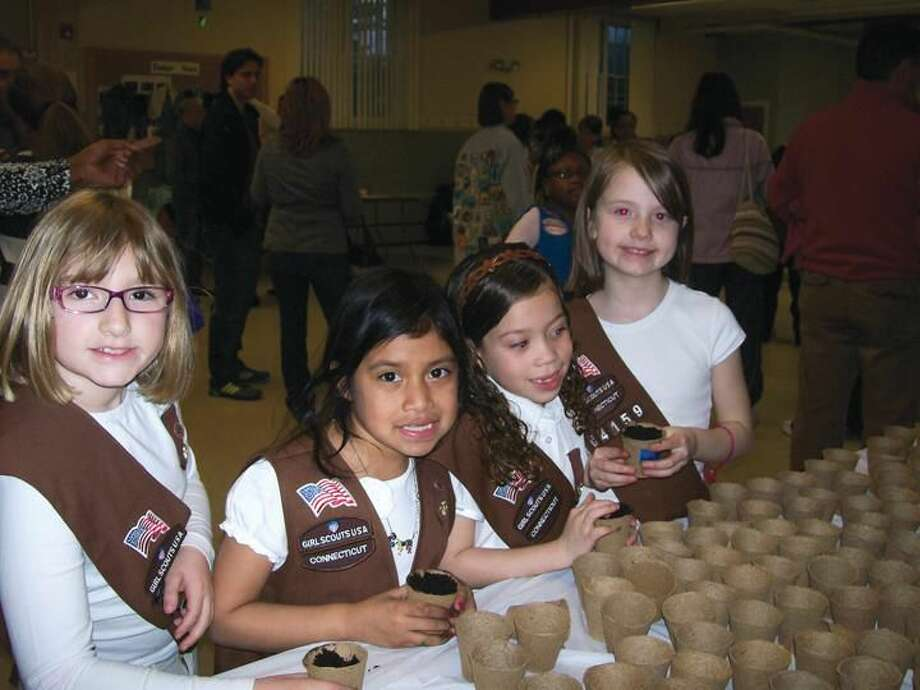 Photo by Lynn Fredricksen Left to right, Brownie scouts Audrey Epstein, Ally Gordon, Niydia Cintron and Mariella Herman, participated in a seed planting activity as part of the Girl Scouts of America's 100th anniversary celebration held at Dunbar Hill United Church of Christ recently. About 100 present and former scouts attended the event.
