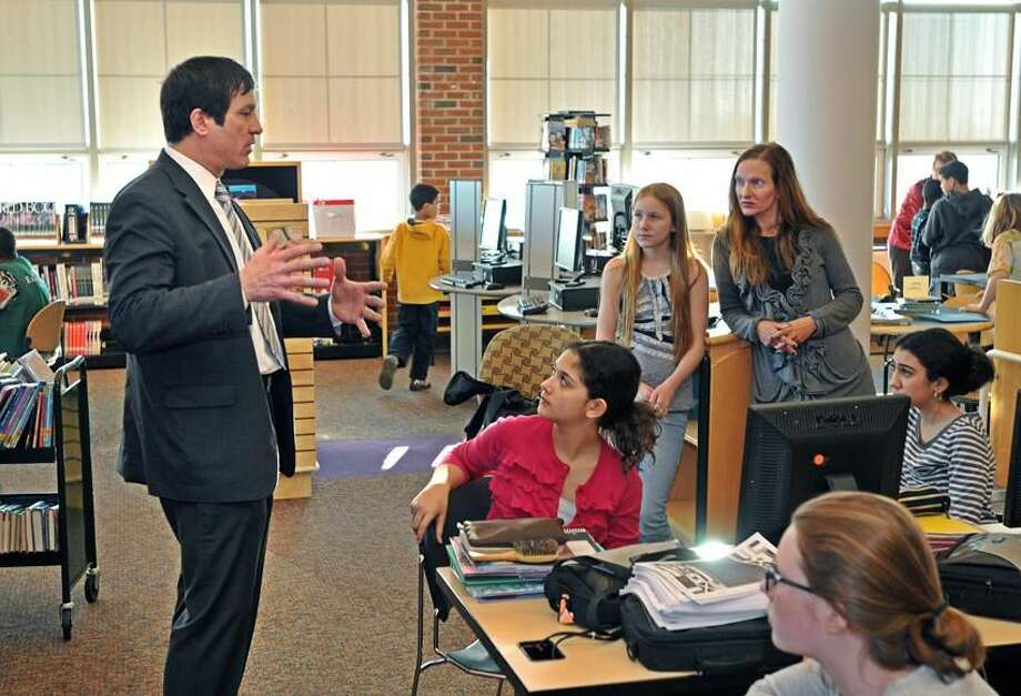 """Kevin J. Paul, a financial adviser with Edward Jones of Cheshire, talks to students at Wintergreen Interdistrict Magnet School in Hamden about funding options for a theme restaurant they are working on called """"We Are the World."""" Peter Casolino/New Haven Register"""