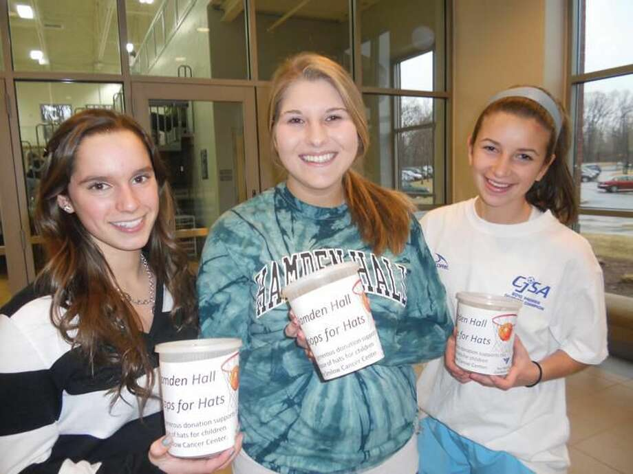 Submitted Photo Senior Molly Teplitzky of Woodbridge, sophomore Sara Bennett of Hamden and freshman Doria Weiss of Orange baked cookies and set up a donation table at two recent Hamden Hall boys' varsity basketball games at the Beckerman Athletic Center.