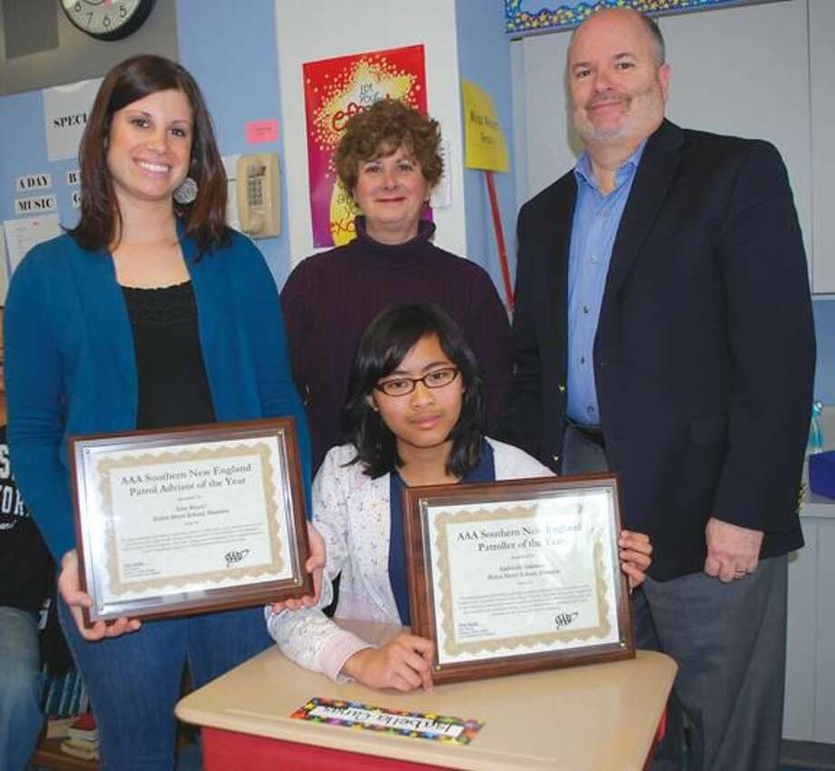 Submitted photo by Adam Bartocetti, Helen Street School Gabrielle Sukmono, seated, a Helen Street School sixth grader, has been named AAA Southern New England's School Patroller of the Year. The patrol advisor, Lisa Meyer, standing at left, has also been named AAA's School Advisor of the Year. Fran Mayko, AAA Public Affairs Manager, center, presented plaques to Ms. Meyer and Ms. Sukmono during an informal ceremony at the 285 Helen Street School. At right is Principal Michael Lorenzo.