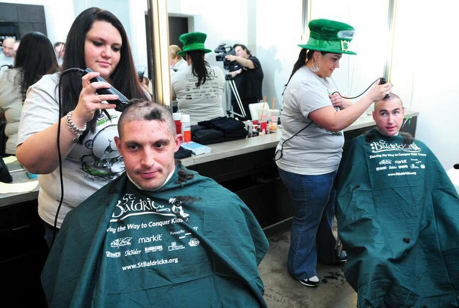 North Haven Police Officer Val Queiroga (left) has his head shaved by Kathleen Rocheleau and fellow Officer P.J. Cormier (right) has his head shaved by Madison Adamo during the St. Baldrick's Foundation fundraiser at G Salon in North Haven on 3/4/2012.Photo by Arnold Gold/New Haven Register AG0442A