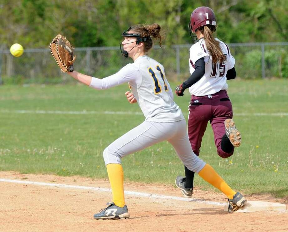North Haven's Brittany Murray is safe at first as East Haven's Amanda Jessey waits for the throw. Mara Lavitt/New Haven Register