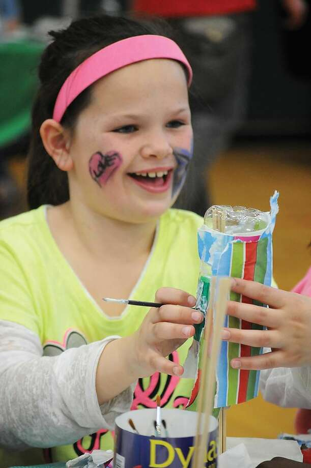 Jenna Sullivan 9, of Hamden, makes a vase from a recycled bottle at the Earth Day Celebration at Hamden Middle School..Melanie Stengel/Register
