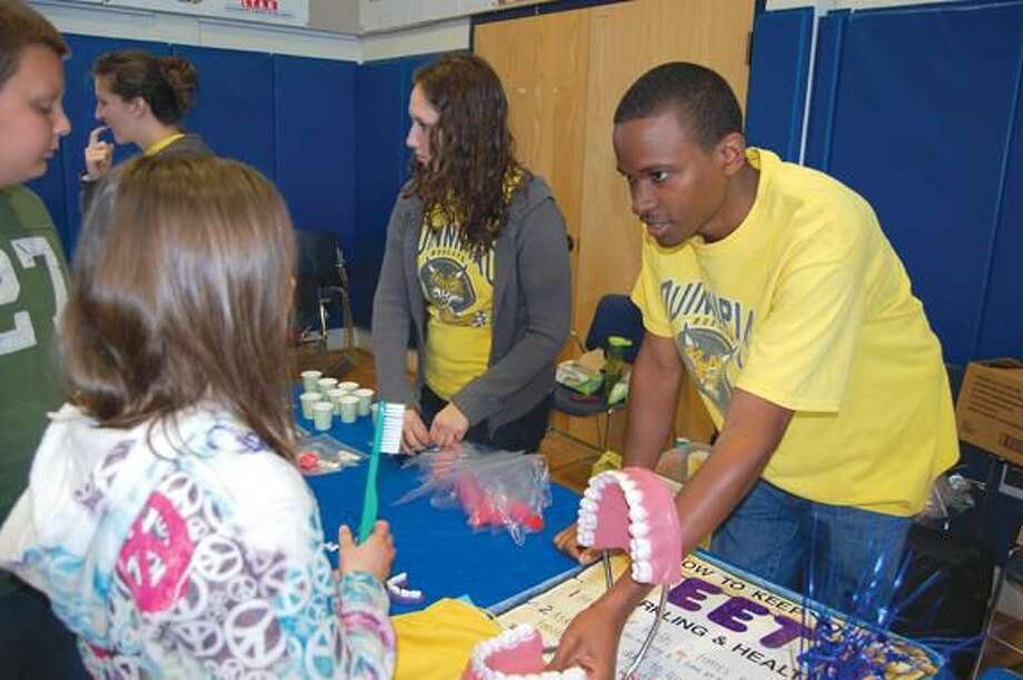 Submitted Photo Quinnipiac University physician assistant student Jaret Williams, right, provided information about the importance of dental health to a student at the Earth Day Health Fair at ACES Mill Road School in North Haven on April 27. Dana Shuriff, another Quinnipiac physician assistant student is next to Williams.