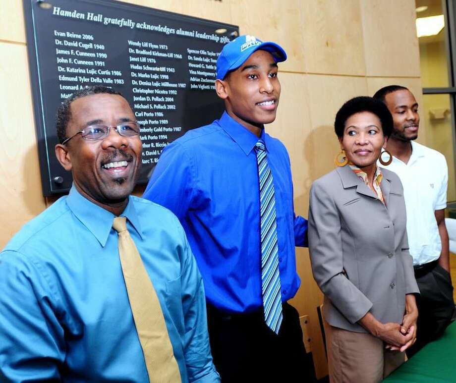 Hamden Hall basketball player Darren Payen, center, signed a national letter of intent to play basketball for Hofstra University at the Beckerman Athletic Center in Hamden. He is pictured with his father Jean-Filbert Payen, left, mother Solange Payen, right, and brother Fred Payen, far right. Photo by Arnold Gold/New Haven Register