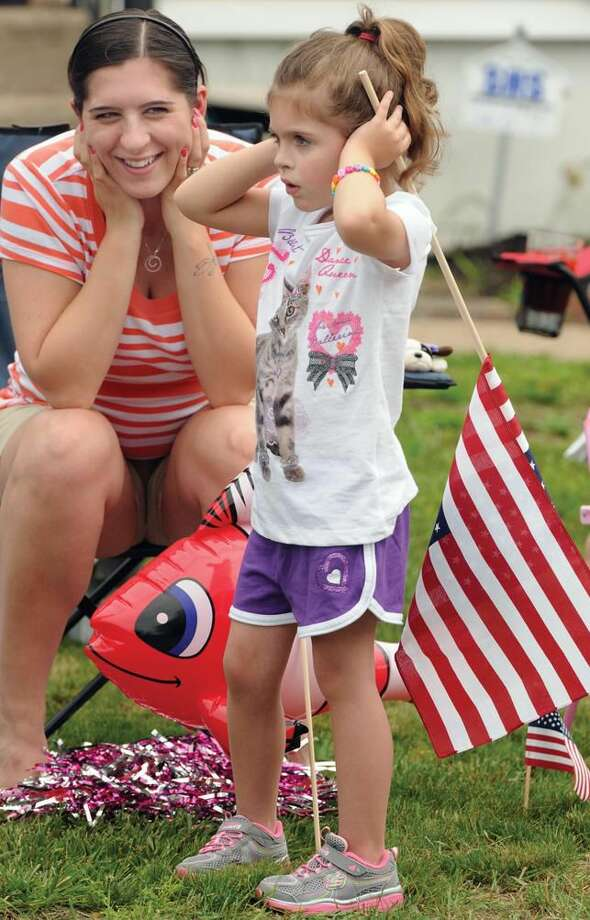 North Haven Memorial Day Parade. Kate Scalesse of North Haven and her daughter Isabella age 5 as a drum corps with muskets goes by. Mara Lavitt/New Haven Register5/26/12