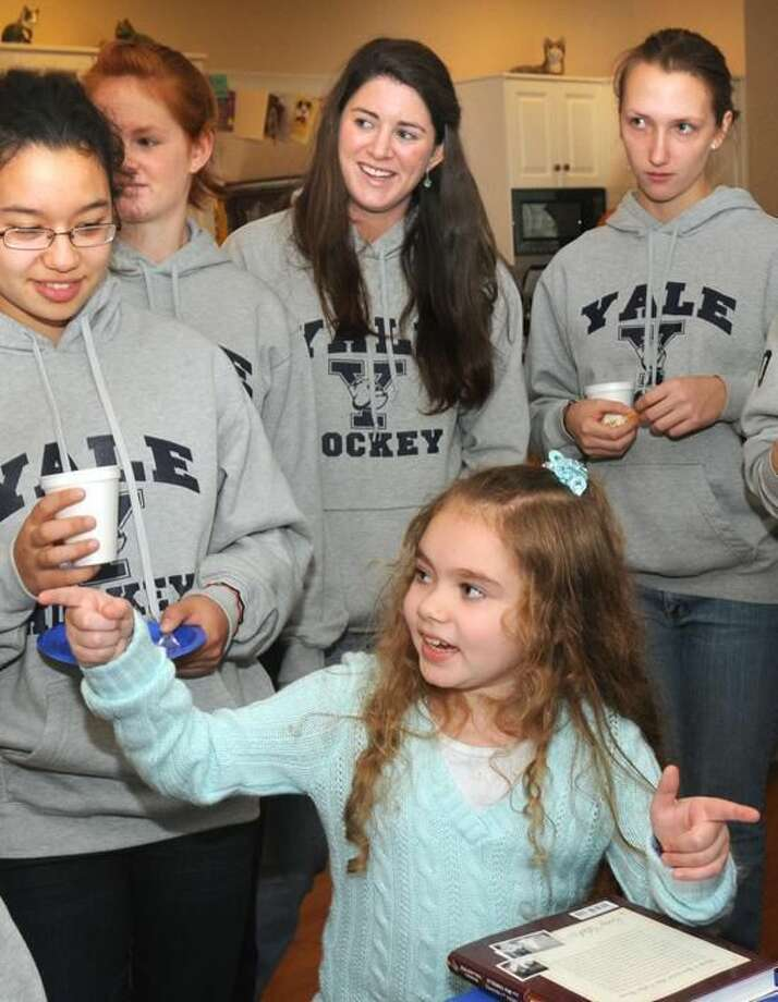 """The Yale women's hockey team, including Aleca Hughes (center), """"adopted"""" nine-year-old Giana Cardonita of Guilford, who had a benign brain tumor removed. On Thursday, Hughes was honored as the ECAC Hockey Mandi Schwartz Student-Athlete of the Year. (Mara Lavitt/Register file photo)"""