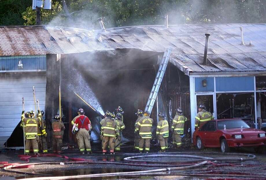 North Haven—North Haven firefighters finish extinguishing a three alarm blaze at 332 Old Maple Avenue. Peter Casolino/New Haven Register 06/18/2012