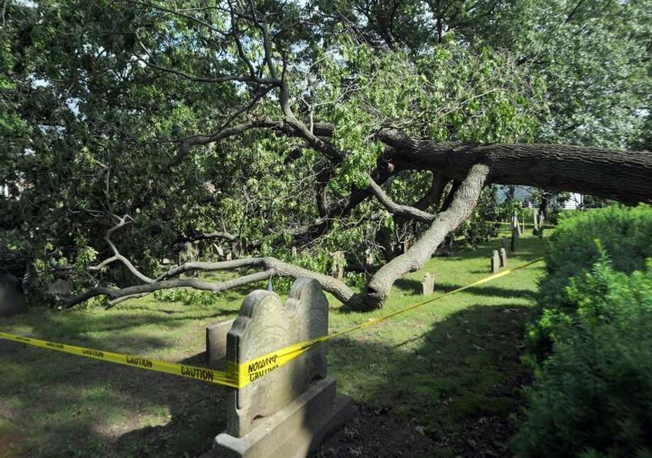 A large tree fallen on headstones in the cemetery on the North haven Green. Photo by Peter Hvizdak/New Haven Register