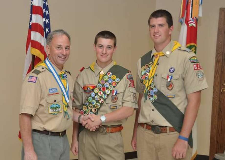 Submitted Photo Scoutmaster Bill Earley congratulates Troop 610 Eagle Scouts Patrick Geirin and Mark Vannoorbeeck.