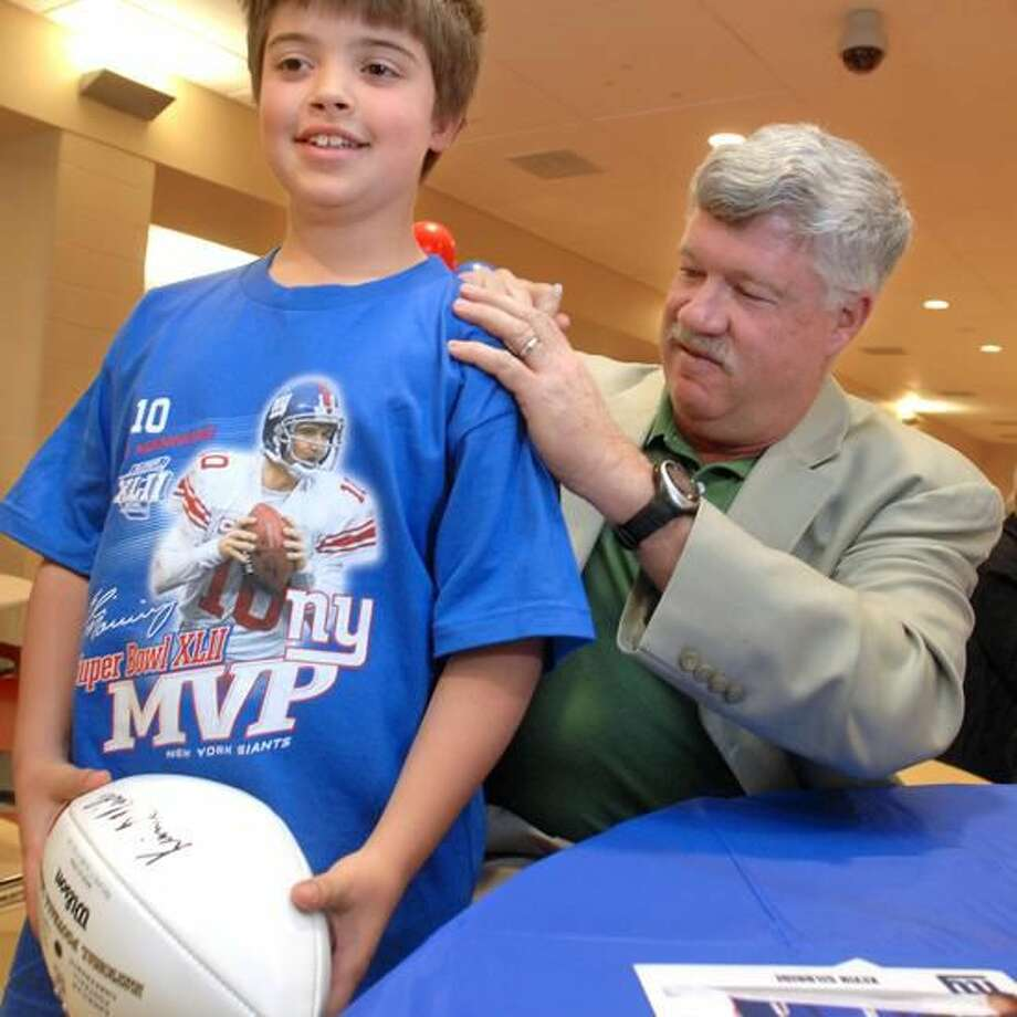Register file photo New York Giants offensive coordinator and North Haven native Kevin Gilbride signs Marc Riccitelli's, 9, T-shirt at North Haven High School.