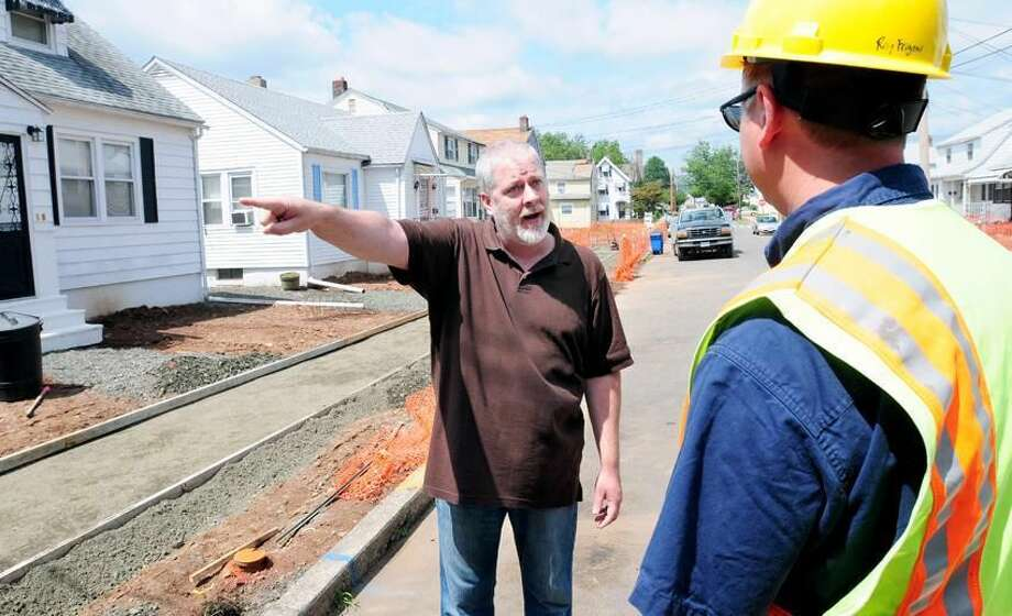 Troy McNulty, center, of 16 Marlboro St. in Hamden argues with Raymond Frigon Jr., right, environmental analyst with the state DEEP, about the need to remediate the soil in McNulty's front yard. Photo by Arnold Gold/New Haven Register