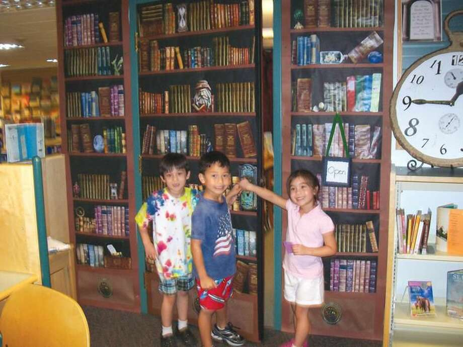 Photo by Lynn Fredricksen Left to right: Tai Moffat, 7, of North Haven; Brian Hersch, 6, of Hamden; and Hanako Moffat, 5, of North Haven, prepare to open the Secret Door as part of a summer reading program in the Children's Department at the North Haven Library.