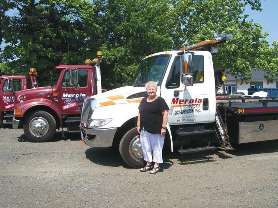 Photo by Lynn Fredrickson Mary Jane Mulligan stands with three of the trucks she and her family own through their business, Merola Motors.
