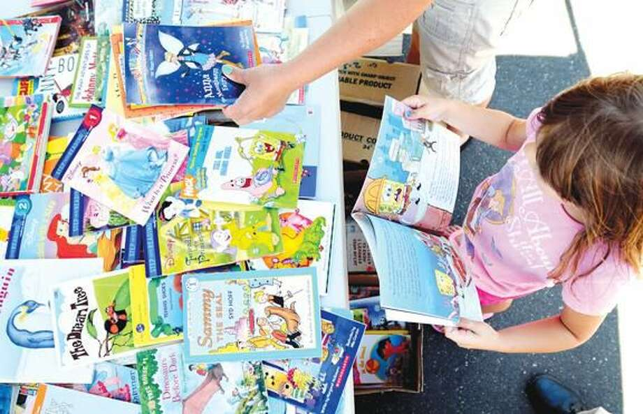 Photo by Arnold Gold Kaitlyn Vincent, 6, of East Haven picks out a Sponge Bob book at the Experience Corps booth at the Hamden Farmer's Market on 7/6/2012.