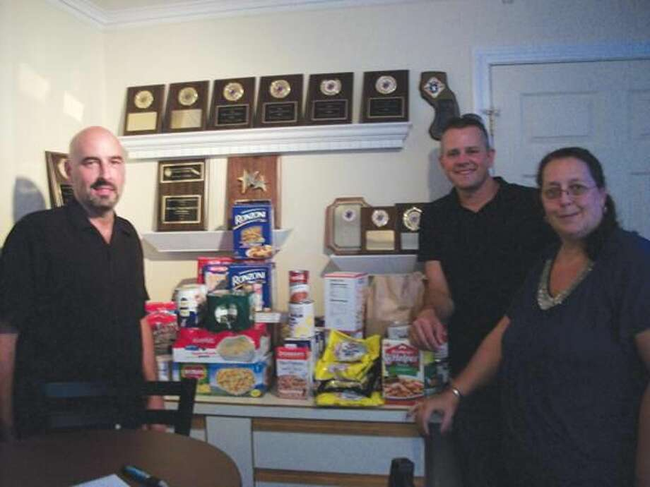Photo by Lynn Fredricksen Connecticut Valley Litho Club members Dave Signore, Sue Mulqueen and Corey Greco organized piles of food donated at a recent food drive the club coordinated in conjunction with the Knights of Columbus. The event was held at the Columbus Club on Church Street.