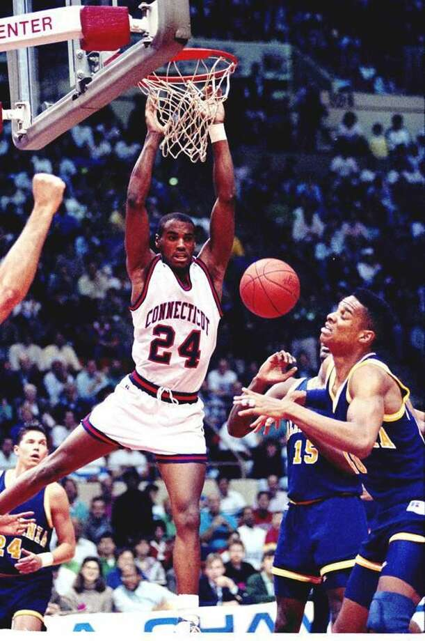 UConn's Scott Burrell of Hamden dunks the ball past Byrant Walton, right, and Brian Hendrick (15) of the University of California in the UConn-California game in the second round of the NCAA East Regional playoffs in Hartford, Conn., Saturday, March 17, 1990. (AP Photo/Bob Child)