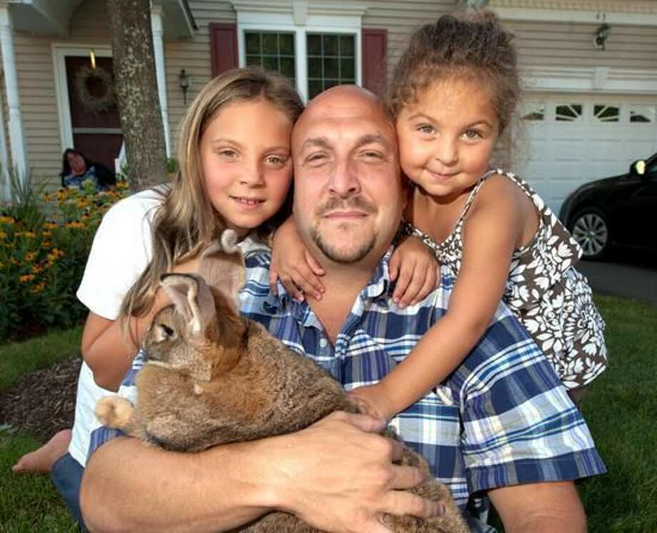 Kayden, her father, Josh, and her sister, Madison Lydsky, pose with Sandy the bunny. VM Williams/Register