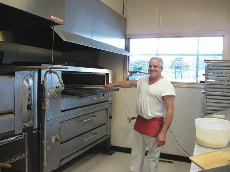 Photo by Lynn Fredricksen Joe Abate, owner and operator of Luigi's Pizza at 323 Washington Avenue, checks on a pie in the pizza oven.