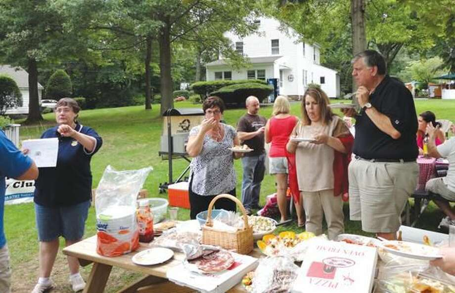 Photo courtesy of David Marchesseault, Rotary PR Chairman Rotary President-Elect Debbie Volain, left, explained the rules for the Day of Wine & Roses competition to wine makers at a picnic Aug. 19 at Ridge Top Club, Inc.