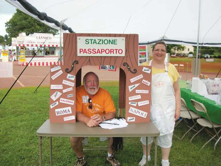 Photo by Lynn Fredricksen Bill Lewis volunteered to man the passport booth in the Kids' Zone at the eighth annual Italian Festival of Angels held last weekend on the grounds of St. Therese Church on Middletown Avenue. He is pictured with Theresa Marino, another member of the Festival Committee.