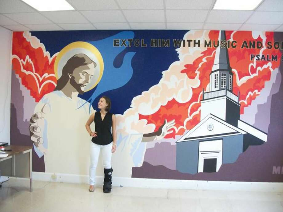 Photo by Lynn Fredricksen Martina Benassi stands in front of the mural she painted to brighten up the choir room at North Haven Congregational Church. She was nearly finished with her project when she suffered a broken foot while playing rugby. She didn't let that stop her. She plans to put the finishing touches on the mural before she returns to college in Boston this fall.
