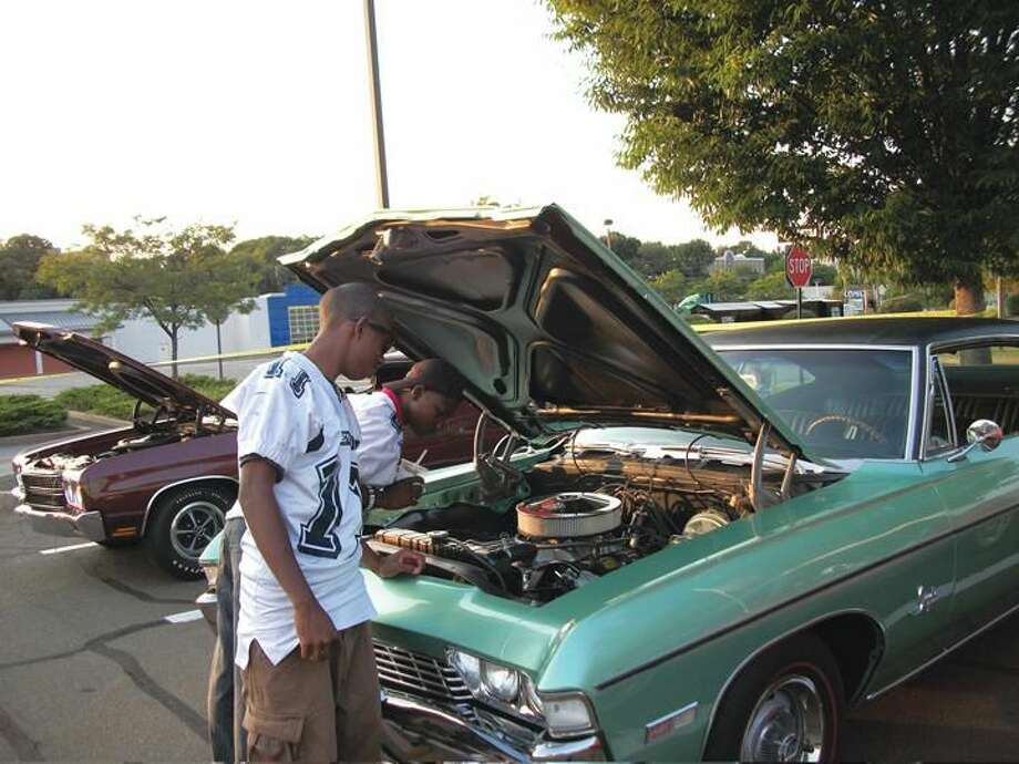 Photo by Lynn Fredricksen New Haven residents Dezjon Streater (leaning into car) and Justin Nelson, both students at Eli Whitney Technical High School, check out a 1968 Chevrolet Impala owned by Don Scialla of Hamden at a car show and fundraiser held recently to benefit the school's football team. Both boys are members of the team.