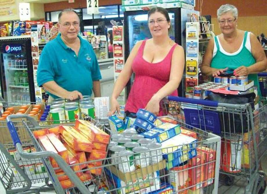 Submitted Photo Shown are Lodge Members Andrew Caporossi, Jen Caputo and Kathy Kelsey purchasing groceries for the Hamden Food Bank.