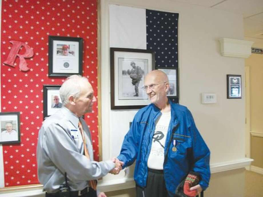 Photo by Lynn Fredricksen U.S. Army veteran Michael Rappa is congratulated by John Ardolino, Engage Life Director at Atria Larson Place on Whitney Avenue. Atria Larson officials honored nine resident veterans recently and presented them each with a Connecticut War Time Service Medal. Both are standing in front of the Wall of Honor where the veterans photos are displayed.