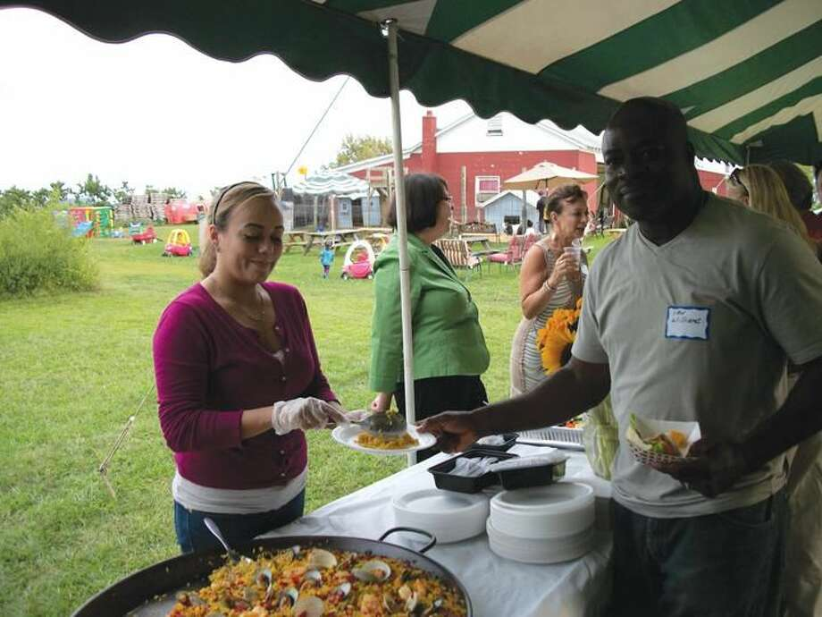 Photo by Lynn Fredricksen Laura Arias of Ibiza Tapas Restaurant and Wine Bar serves up some paella to Hamden Chamber of Commerce member Ian Williams, of Falcon Funding. Both were at a Business After Hours held at Hindinger Farm last week to kick off the Chamber's annual Restaurant Week celebration from Sept. 17 to 23.