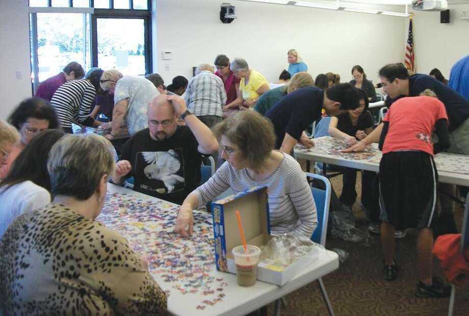 By Lynn Fredricksen The Community Room at the North Haven Public Library was abuzz with activity Saturday morning as eight teams scrambled to see which would be the first to assemble a 1000-piece jigsaw puzzle.