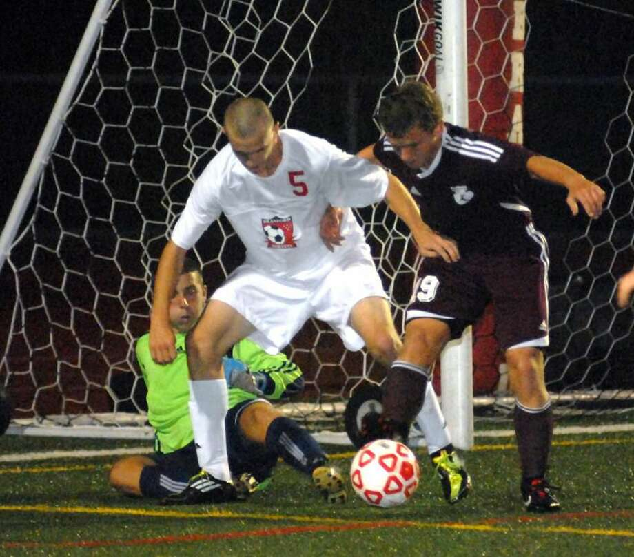 Photo by Dave Phillips North Haven goalie Zach Tabak makes a save and Dillon McManus kicks the ball away from Branford's Aaron Radulski during the Hornets' 1-0 victory last Wednesday at the James MacVeigh Alumni Athletic Complex in Branford.
